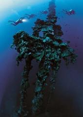 dramatic photo of divers using scuba to explore sunken shipwreck