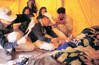 蹲跪在地上為病患治療