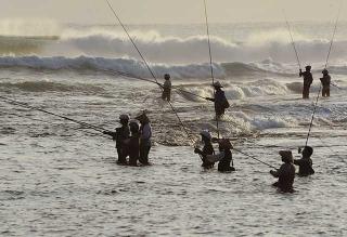 早晨站立海浪中釣魚